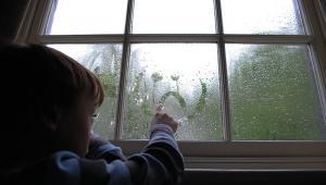 child drawing sad face on window